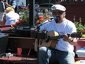 A man singing and playing the guitar at Pier 49